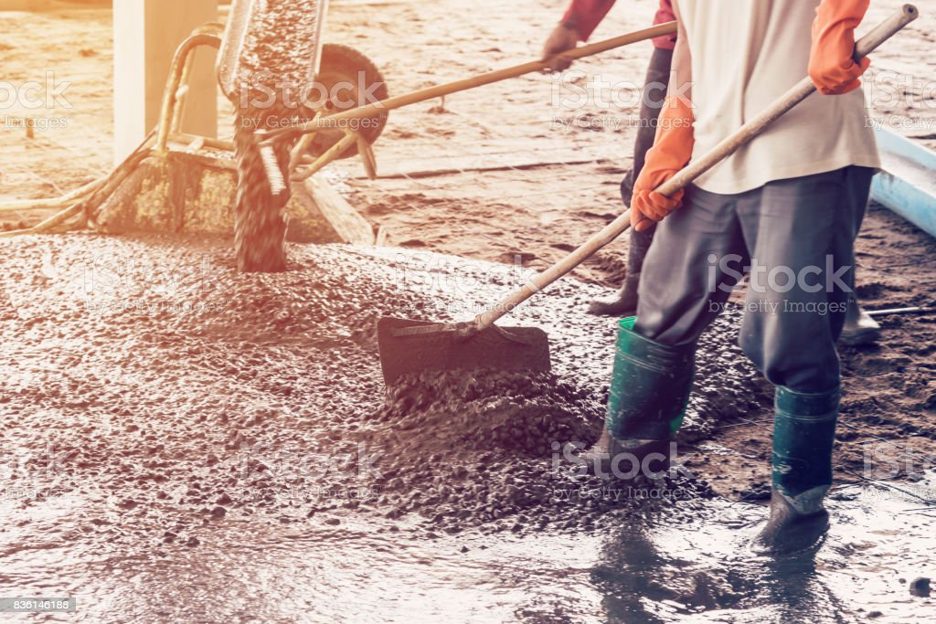 man workers spreading freshly poured concrete mix on building with vintage tone. stock photo