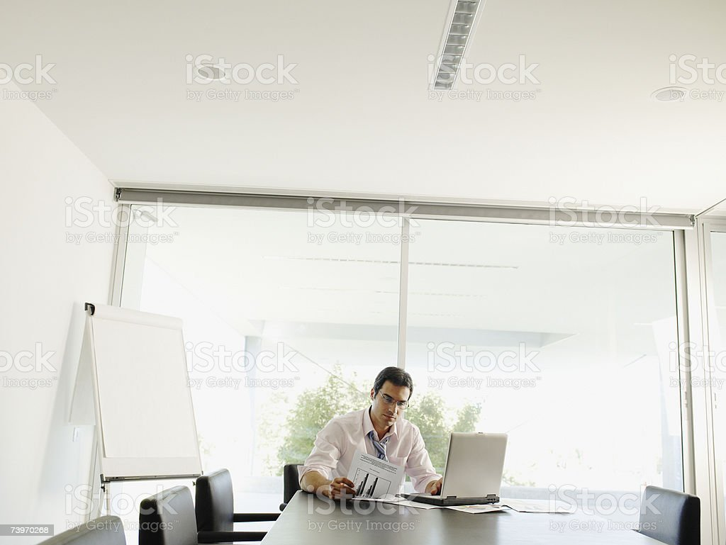 Man working alone in a boardroom with his laptop royalty-free stock photo