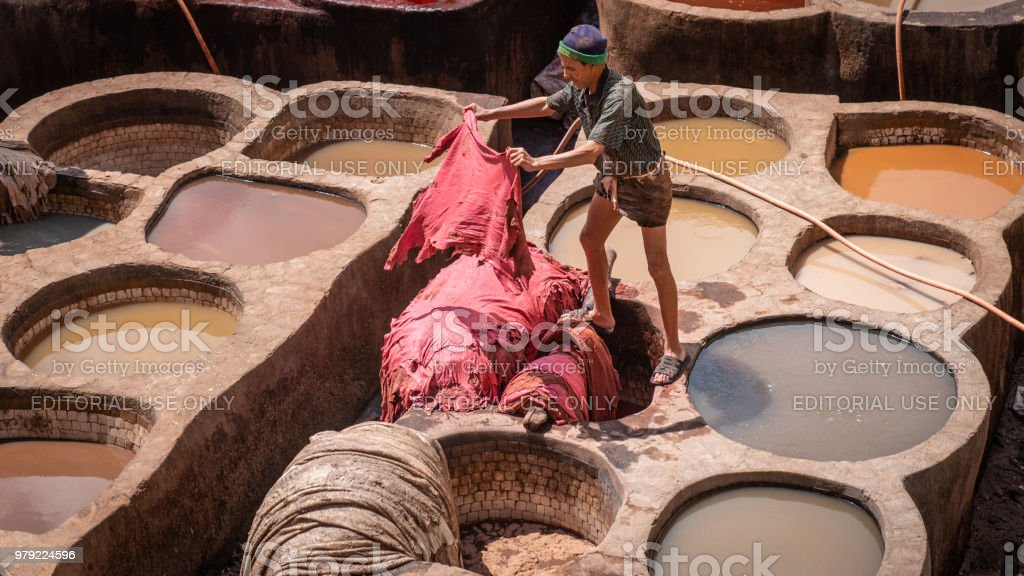 Man working as a tanner in the dye pots at leather tanneries viewed...