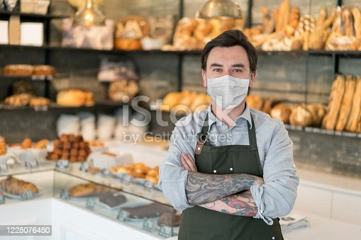 Portrait of man working at a bakery wearing a facemask to avoid the coronavirus – COVID-19 lifestyle concepts