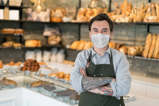 man working at a bakery wearing a facemask to avoid the coronavirus - small business owner stock pictures, royalty-free photos & images