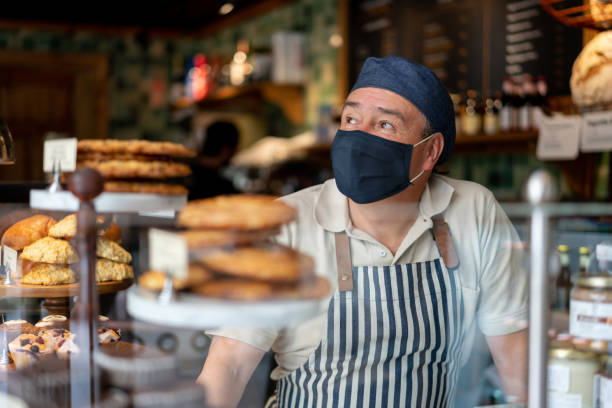 man working at a coffee shop wearing a facemask - servizi essenziali foto e immagini stock