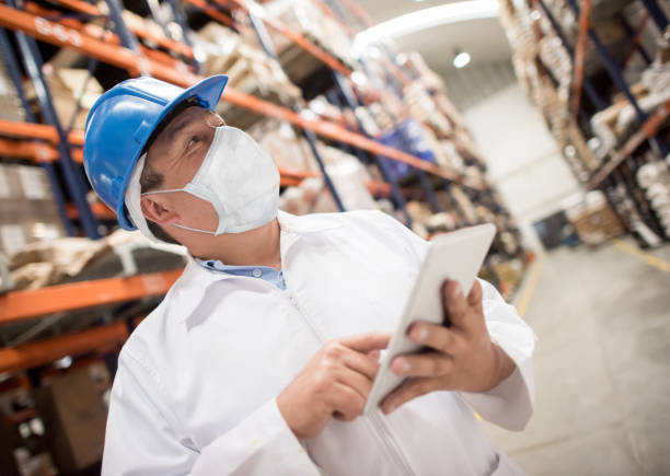 Man working at a distribution warehouse wearing a facemask to avoid COVID-19 stock photo