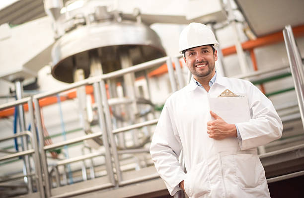 Man working at a factory Latin man working at a factory wearing a helmet and robe and smiling to the camera food warehouse stock pictures, royalty-free photos & images
