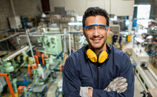 Latin American man working at a metal factory and wearing protective wear