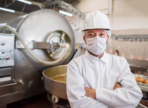 man working at a food factory - livsmedelstillverkningsfabrik bildbanksfoton och bilder