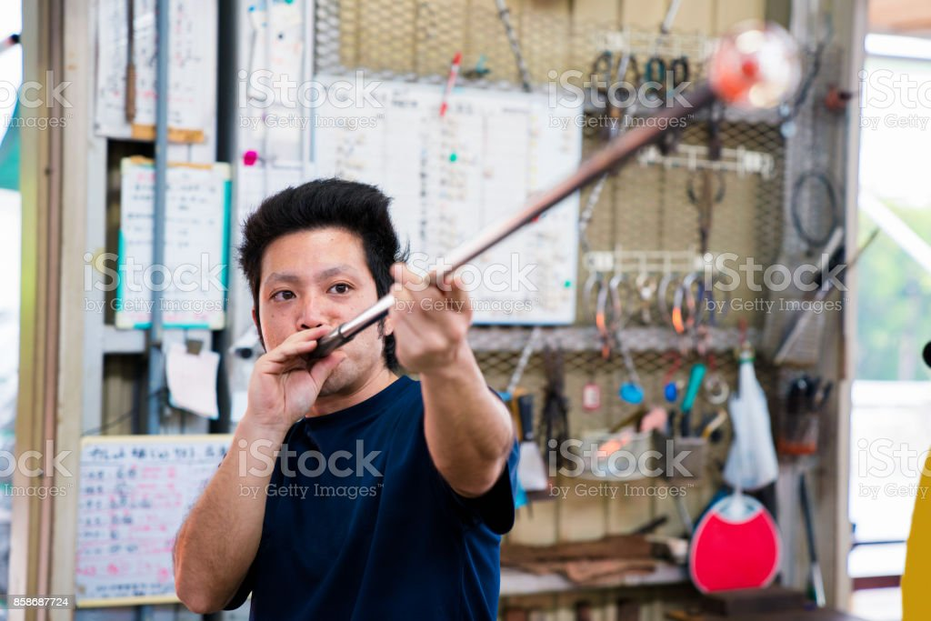 Man working at a glass factory stock photo