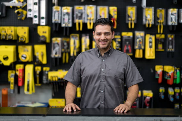 Man working at a hardware store Portrait of a happy Latin American man working at a hardware store and looking at the camera smiling hardware store stock pictures, royalty-free photos & images