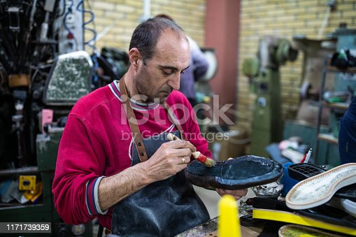 Mature man sitting in shoe factory and  gluing little leather parts of  shoes, using brush