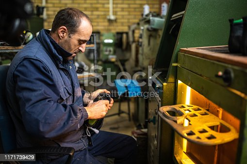 Mature man sitting on chair and checking sole of shoes in special machine at shoe factory