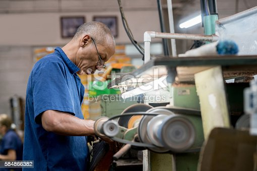 Man working at a shoe-making factory in the production line
