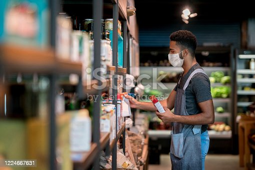 Man working at a supermarket restocking the shelves and wearing a facemask - COVID-19 lifestyle concepts