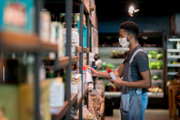 Man working at a supermarket restocking the shelves and wearing a facemask stock photo