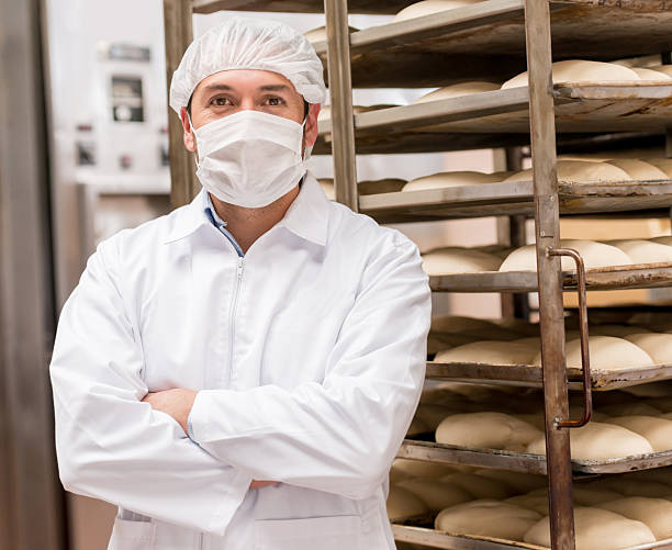 Man working at an industrial bakery Man working at an industrial bakery wearing full uniform - food factory concepts food warehouse stock pictures, royalty-free photos & images
