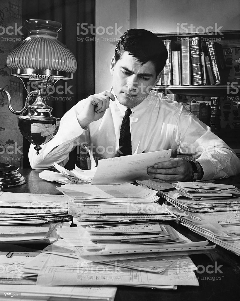 Man working at desk covered with files 免版稅 stock photo