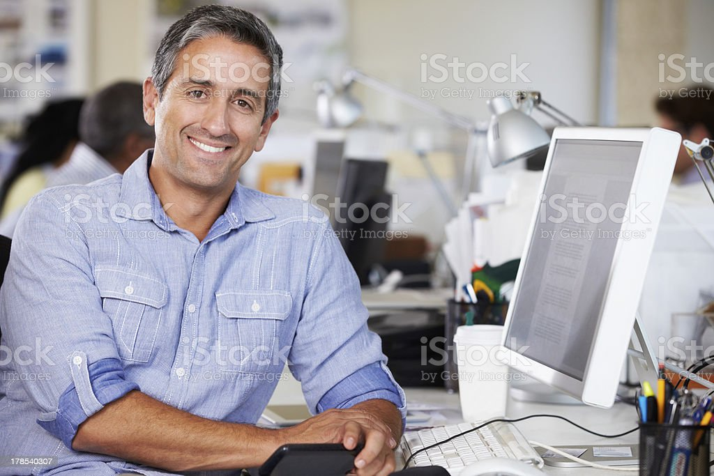 Man Working At Desk In Busy Creative Office stock photo