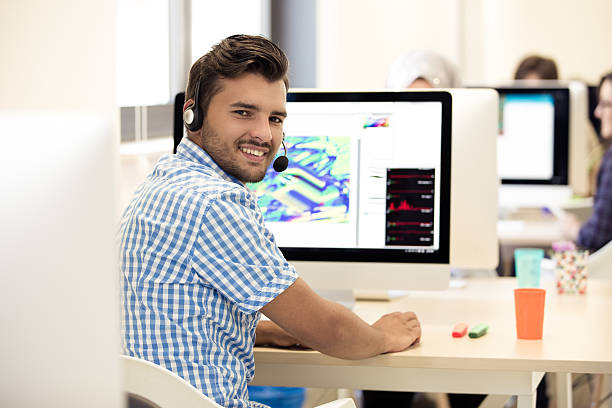 homme travaillant au bureau en bureau créatif occupé - graphisme photos et images de collection