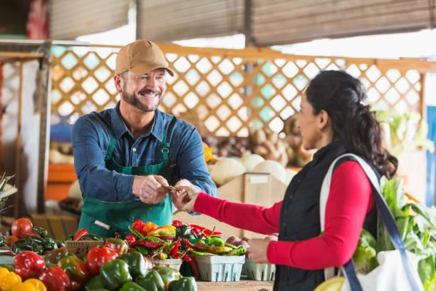 Man working at farmer's market taking cash from customer stock photo