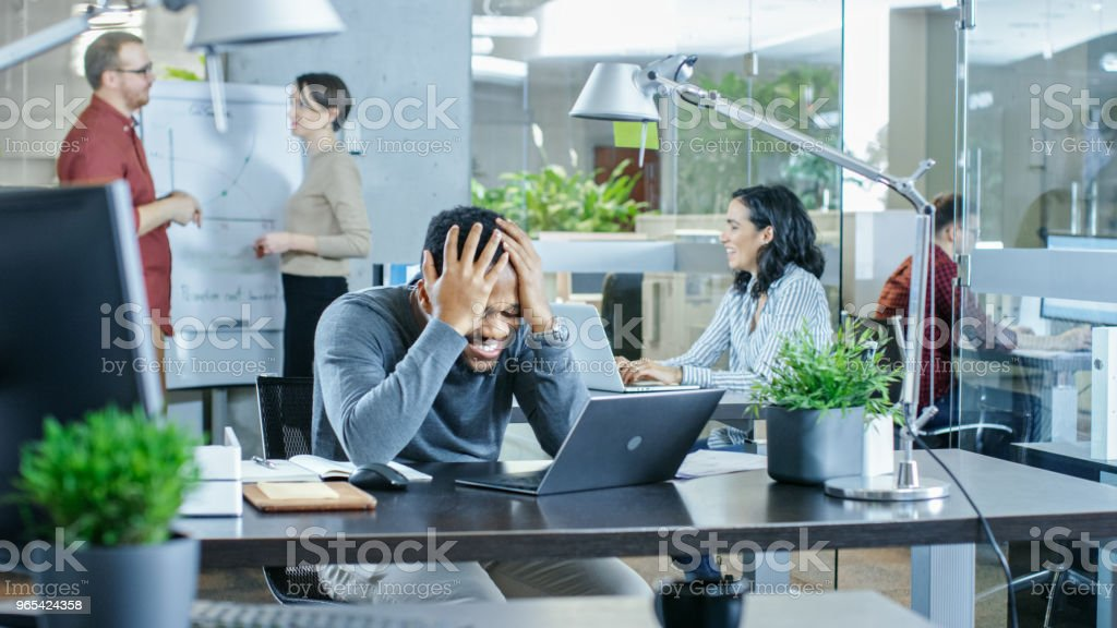Man Working at His Desk Working on a Laptop, Encounters Bad Mistake and Holding His Head in Hands. In the Background Creative Young People Doing Their Jobs. Modern Bright Office. royalty-free stock photo