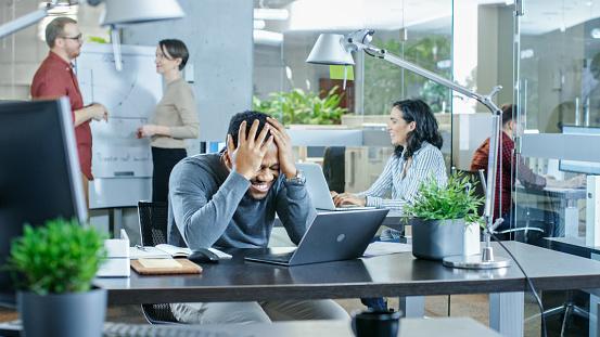 남자는 노트북에서 일 하는 그의 책상에서 일에서 나쁜 실수 하 고 손에서 그의 머리를 잡고 배경 창조적인 젊은이에 그들의 일을 하 고 현대 밝은 사무실 감정에 대한 스톡 사진 및 기타 이미지