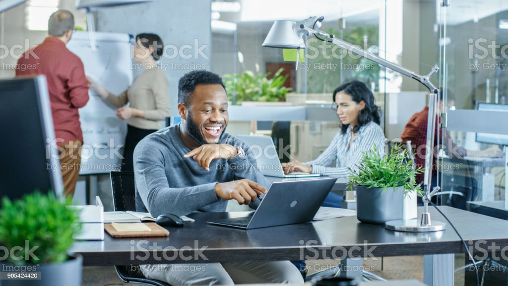 Man Working at His Desk Working on a Laptop, Encounters Funny Mistake and Laughs. In the Background Creative Young People Doing Their Jobs. Modern Bright Office. royalty-free stock photo