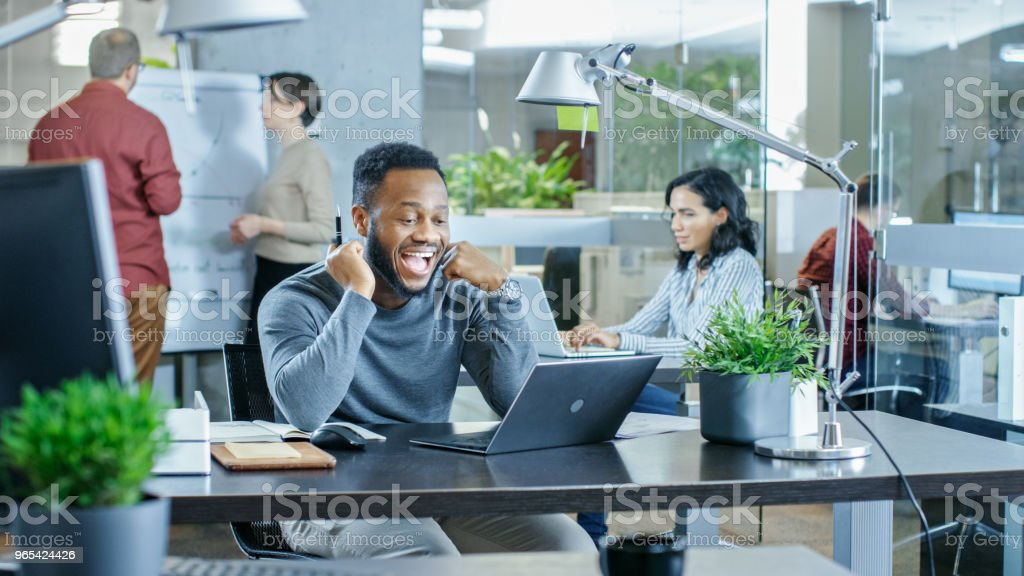 Man Working at His Desk Working on a Laptop, Encounters Funny Mistake and Laughs. In the Background Creative Young People Doing Their Jobs. Modern Bright Office. zbiór zdjęć royalty-free