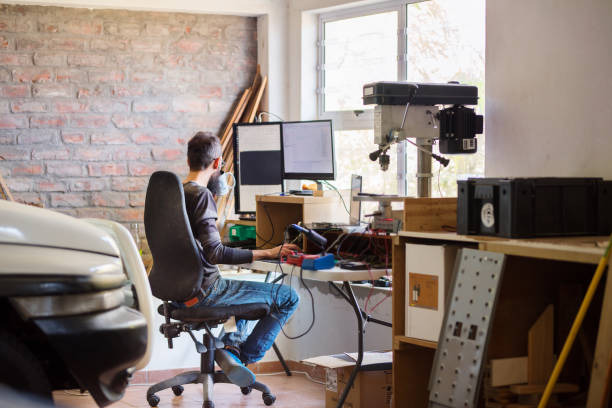 Man working at his temporary home office in his garage stock photo