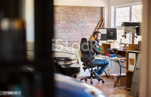 Bearded man working while sitting at a desk in his garage