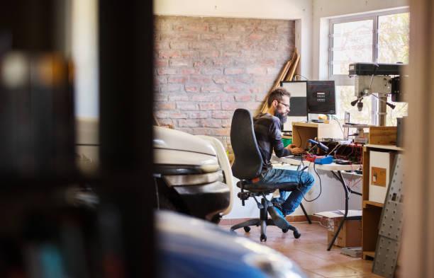Mann arbeitet in seinem temporären Home Office in seiner Garage – Foto