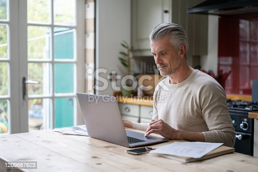 Portrait of an adult man working online at home on his laptop computer – lifestyle concepts