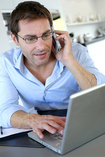 Man working at home with laptop and mobile phone stock photo