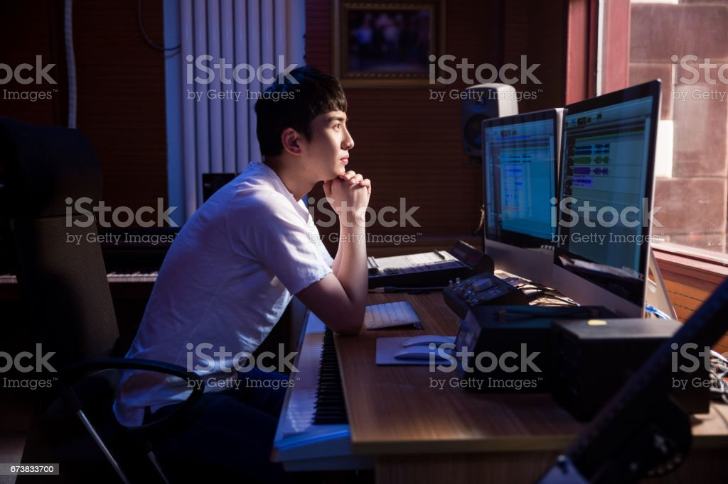 Man working at mixing panel in a recording studio stock photo