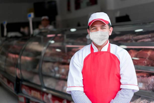 Mann, der in der Metzgerei arbeitet und eine Gesichtsmaske trägt, um das Coronavirus zu vermeiden – Foto