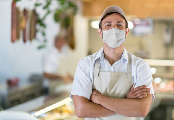 Man working at the butcher's shop wearing a facemask to avoid the coronavirus stock photo