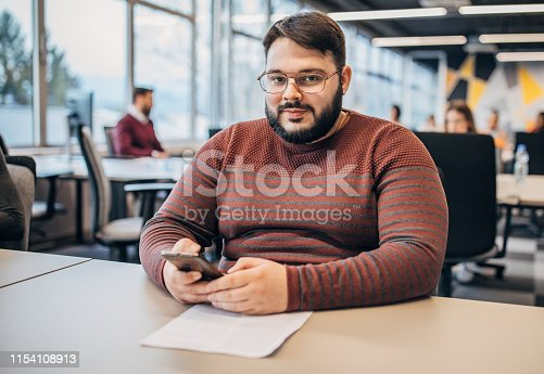 One young overweight man with reading glasses sitting at the office, using smart phone and reading documents.