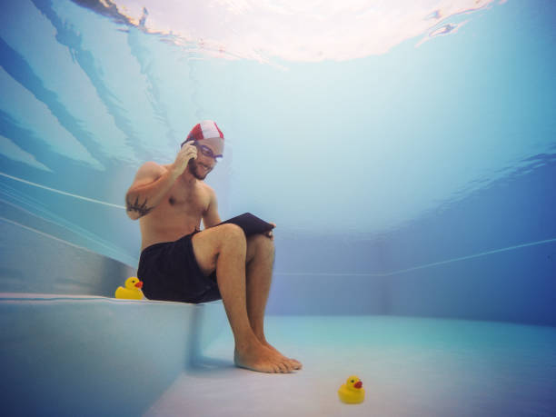 man working at the telephone underwater - smartphone addiction not groups stock pictures, royalty-free photos & images