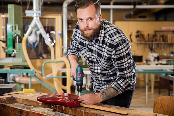 mann arbeitet in der werkstatt mit gitarre - baroque tattoo stock-fotos und bilder