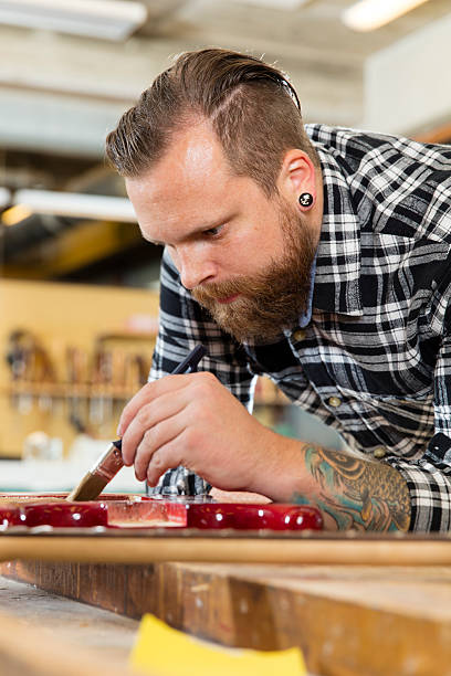 mann arbeitet in der werkstatt mit musikinstrumenten - baroque tattoo stock-fotos und bilder
