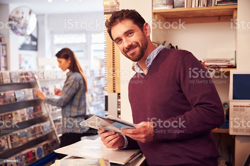 Man working behind the counter at a record shop, portrait stock photo
