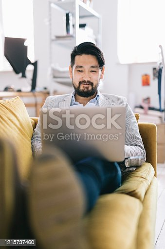 istock Man working from a couch 1215737460