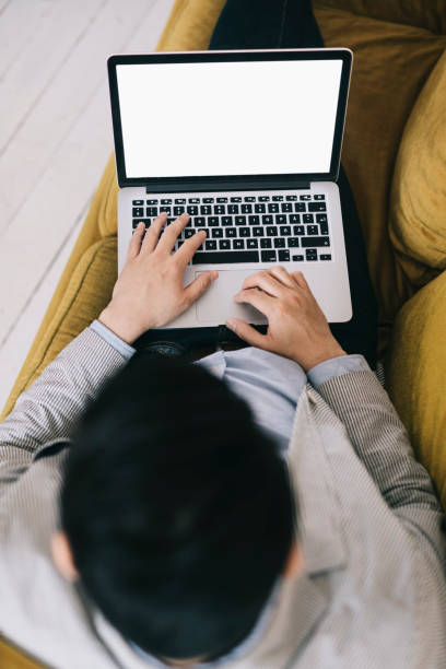 Man working from a couch with empty screen on the laptop stock photo