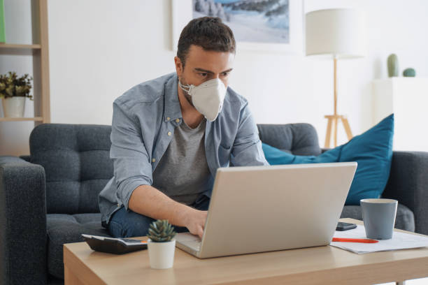 Man working from home and worried about covid-19 coronavirus stock photo