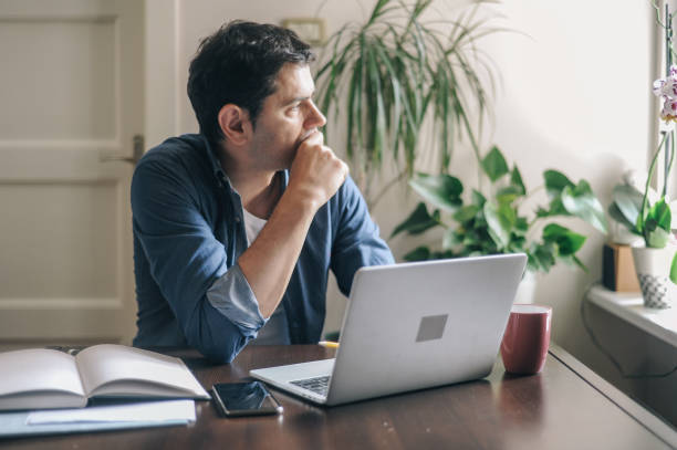 Man working from home due to the COVID-19 pandemic stock photo