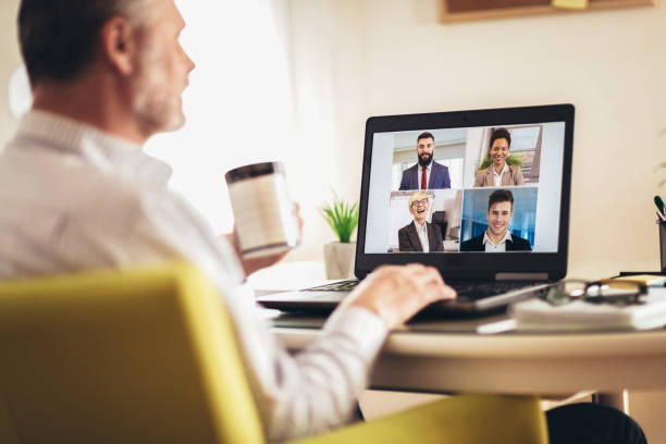 Man working from home having online group videoconference on laptop stock photo