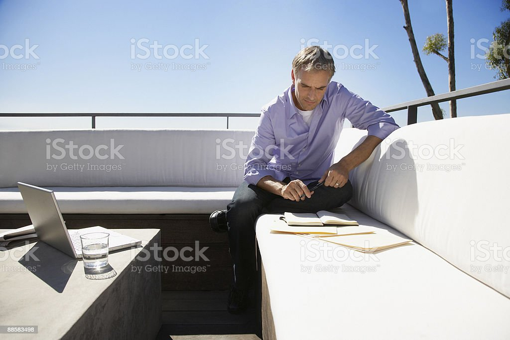 Man working from home on balcony royalty-free stock photo