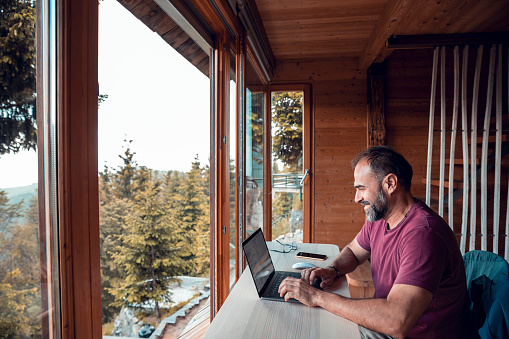 Close up of a mid adult man working on a laptop from his cabin in the woods