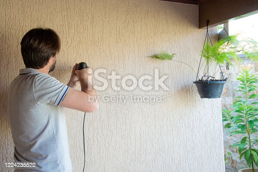 man working from home using drill on the wall