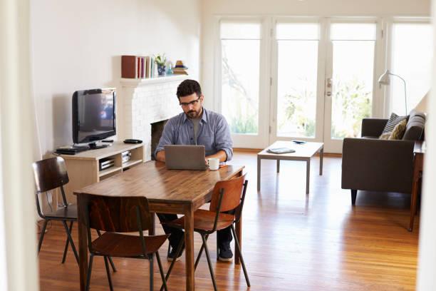 man working from home using laptop on dining table - オフィス外勤務 ストックフォトと画像