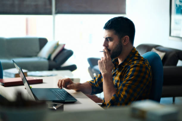 Man Working From Home With Computer And Smoking Cigarette stock photo