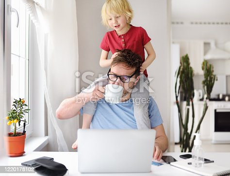 Man working from home with laptop during quarantine. Home office and parenthood at same time. Exhausted parent with hyperactive child. Chaos with kids during isolation